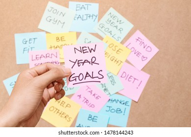 "Motivational word ""New year goals"" on pink card"