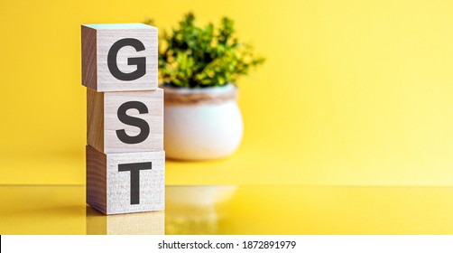 Motivational words: GST in 3d wooden alphabet letters on a bright yellow background with copy space, business concept. GST - Goods and Services Tax.