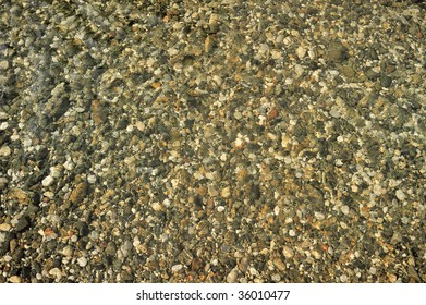 Lot of motley pebbles in a shallow rippling water, bottom of river