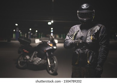 Moto biker is showing a thumbs up on night parking background.