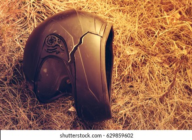 Moto helmet on grass with crack from accident at sunset. Toned