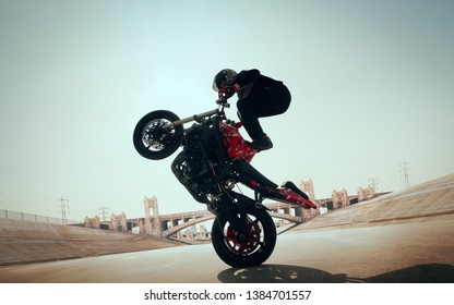 Moto rider making a stunt on his motorbike. Biker doing a difficult and dangerous stunt.