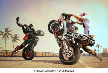 Moto riders making a stunt on his motorbike. Biker doing a difficult and dangerous stunt.