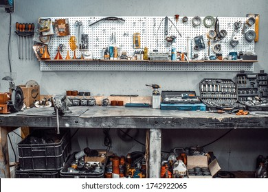 Moto workshop with hand tools. Workbench with sets of keys, screwdrivers, ploskobets, electrical tape, duct tape on the wall. Table with motorcycle parts, vise. Workspace for a joiner, auto mechanic