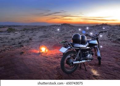 Motobike and two black helmet on desert land with light dots around, sunrise morning background