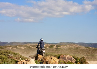 Motobiker riding enduro on Portugal out of road . Sagres cape.