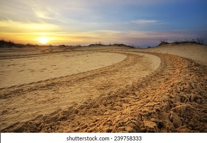Motocross and auto sport track with sunset sky background. Wheel tracks on sand