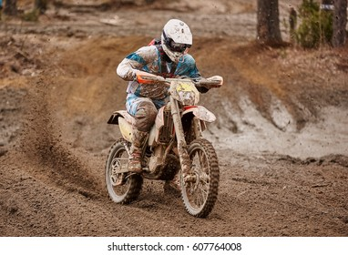 Motocross driver in action accelerating the motorbike  on muddy race track.