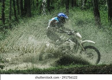 Motocross driver under the spray of mud