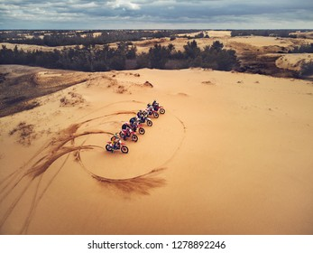 Motocross. People On Motorbikes In Sand Desert Nature On Start Line. Row Of Motorcycles On Sand