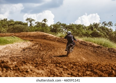 Motocross racer accelerating in dirt track