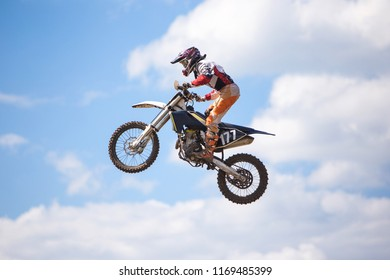 Motocross. Racer jumping against the blue sky