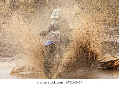 Motocross racer in a wet and muddy terrain in Parola, Finland. Water and mud splashing everywhere and covering the driver completely.