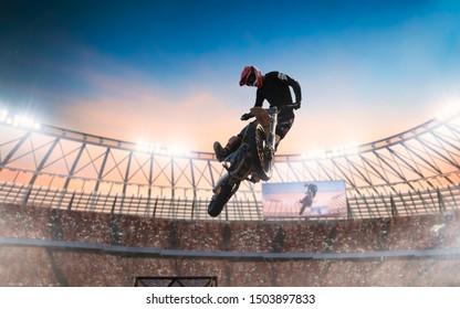 Motofreestyle on professional stadium in sunset. Motocross.