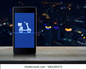 Motor bike icon on modern smart phone screen on wooden table over blur colorful night light city tower, Business delivery service concept