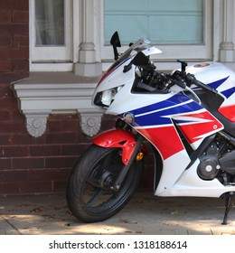Motor bike parked on the verandah of a red brick victorian house. The window and window sill are in the background