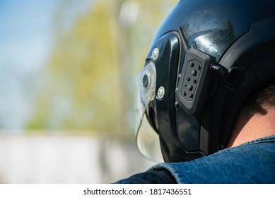 Motor biker helmet with a mobile phone headset close up.