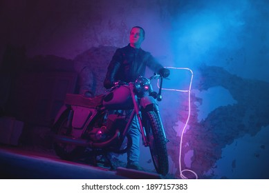 Motor biker in the neon lights on the old brick wall background.