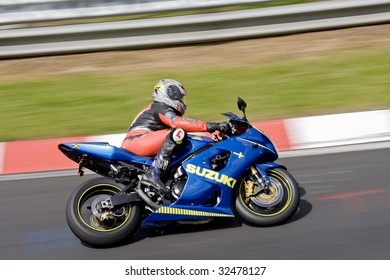 Motor biker on a race circuit speeding round a corner with a race circuit kerb behind