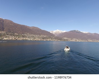 Motor boat at Lago Maggiore close to Ascona Locarno Ticino. CH Switzerland. Drone aerial shot, early spring, very calm water, little snow on mountains in background. 27th March 2016