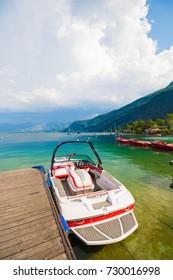 Motor boat near wooden pier on a beautiful mountain lake Wolfgangsee in austrian Alps. Alpine landscape of Austria.