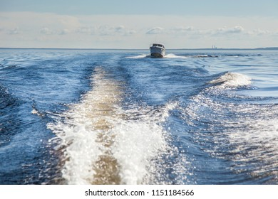 motor Boat sails on the water surface of the lake against the background of clouds