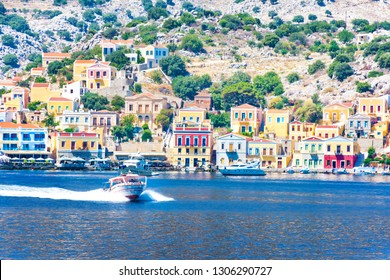 Motor boats and colorful houses in harbor town of Symi (Symi Island, Greece)
