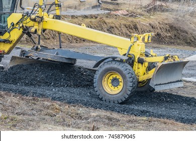 Motor grader with a blade performs the layout of a road crushed stone gravel base