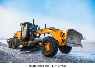 Motor Graders, Grader Road Construction. Industrial machine on construction of roads. Truck moving on dirt country road. Grader is driving along an empty winter road