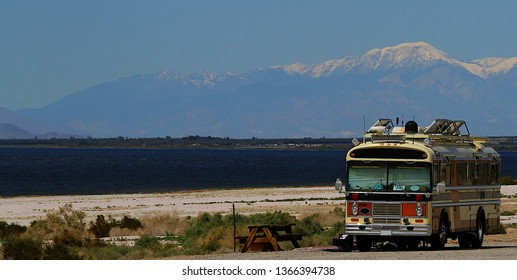 A motor home parked at the Salton Sea which is located in the desert in California. This recreational vehicle. also known as an RV has a retro look and has a beautiful mountain view backdrop.