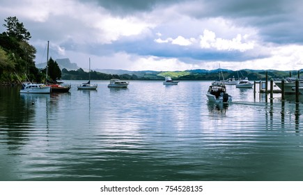 Motor launch motoring out of Whangaroa Harbour marina through moored boats at Far North, Northland, New Zealand, NZ, on a winter day