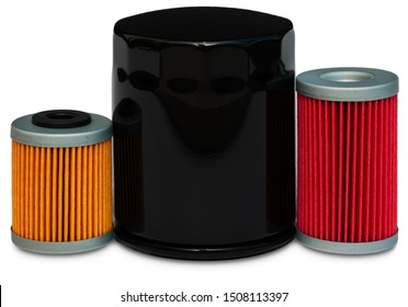 Motor oil filters at white background. Isolated screw-on black engine oil filter with area for copy space placed in the center of the composition, red and yellow insert oil filters — on the sides.
