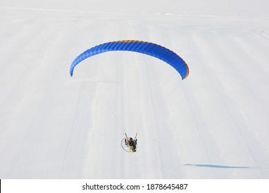 Parapente à moteur volant en hiver dans un paysage blanc-neige vu du ciel