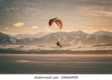 Motor paraglider over the lake with mountains and sky on background, winter sunset landscape, tourist attraction, Liptovska Mara, largest water reservoir in Slovakia (Slovensko), travel destination