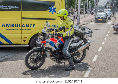 Motor Policeman At Amsterdam The Netherlands 2018 And Ambulance At The Background