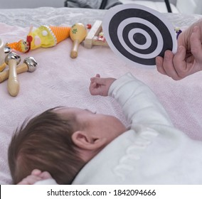 motor skills and early stimulation class with baby and contrasting black and white pictures