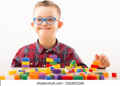 Motortherapie. Junge mit Down-Syndrom spielen mit Spielzeug und Threading-Aktivitäten für die Handtherapie.