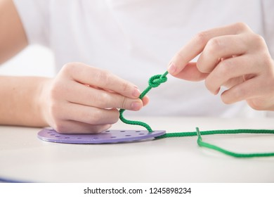 Motor therapy. Child doing threading activities for hand therapy using a threading board.