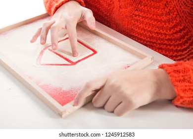 Motor therapy. Child playing with montessori sand tray for hand therapy. Child drawing a house in sand. Educational games for writing practice.