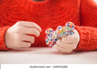 Motor therapy. Child playing with rainbow mesh grape squeeze ball for hand therapy. Educational games for writing practice.