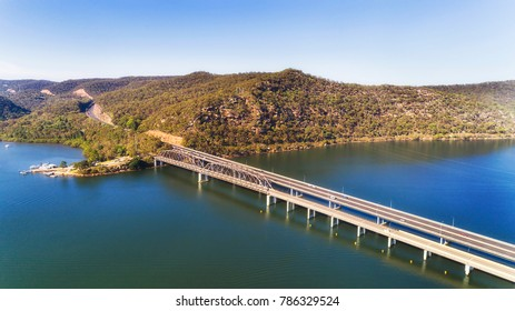Motor vehicle multi lane bridges part of Motorway 1 Sydney to Newcastle over Hawkesbury river on NSW Central coast in australia over still flowing waters on a sunny summer day with passing traffic