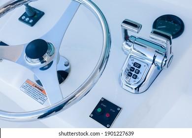 Motor yacht control panel. Steering wheel, gear levers, control button tachometer. Luxury yacht navigation bar.