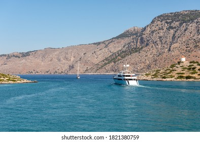 Motor yacht is taking away from blue lagoon at Symi island, Greece