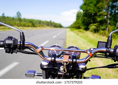 motorbike chrome handlebars of classic vintage motorcycle parked in a road in summer countryside