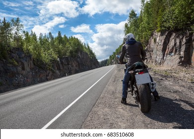 Motorbike driver is ready to start moving on the asphalt route, sitting on motorbike on roadside, rear view