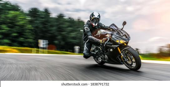 Motorrad auf der Straße schnell fahren. Spaß auf der leeren Autobahn auf einer Motorradfahrt. Kopiere Platz für deinen einzelnen Text. Blureffekt bei schneller Bewegung