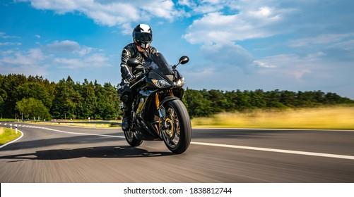 Motorrad auf der Straße reiten. Spaß beim Fahren der leeren Straße auf einer Motorradtour. Kopiere Platz für deinen einzelnen Text. Blureffekt bei schneller Bewegung