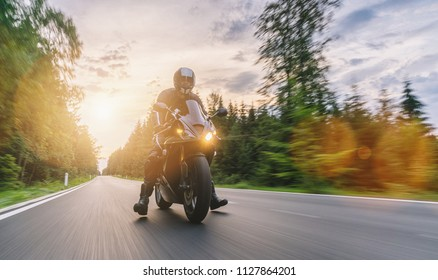 motorbike on the road riding with motion speed. driving on the empty road on a motorcycle tour at sunset. copyspace for your individual text.