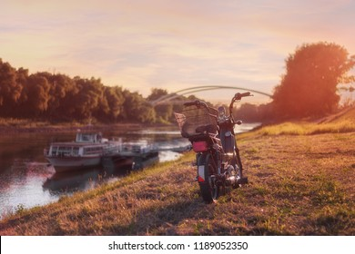Motorbike parked next to a river in golden sunset