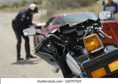 Motorbike with police officer talking with driver in the background